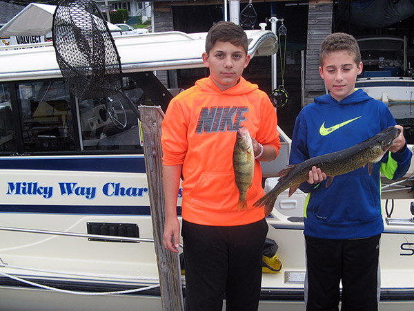 Henderson Harbor Fishing with Milky Way Charters - Johnny & Friend Holding A Couple of Their Catch!