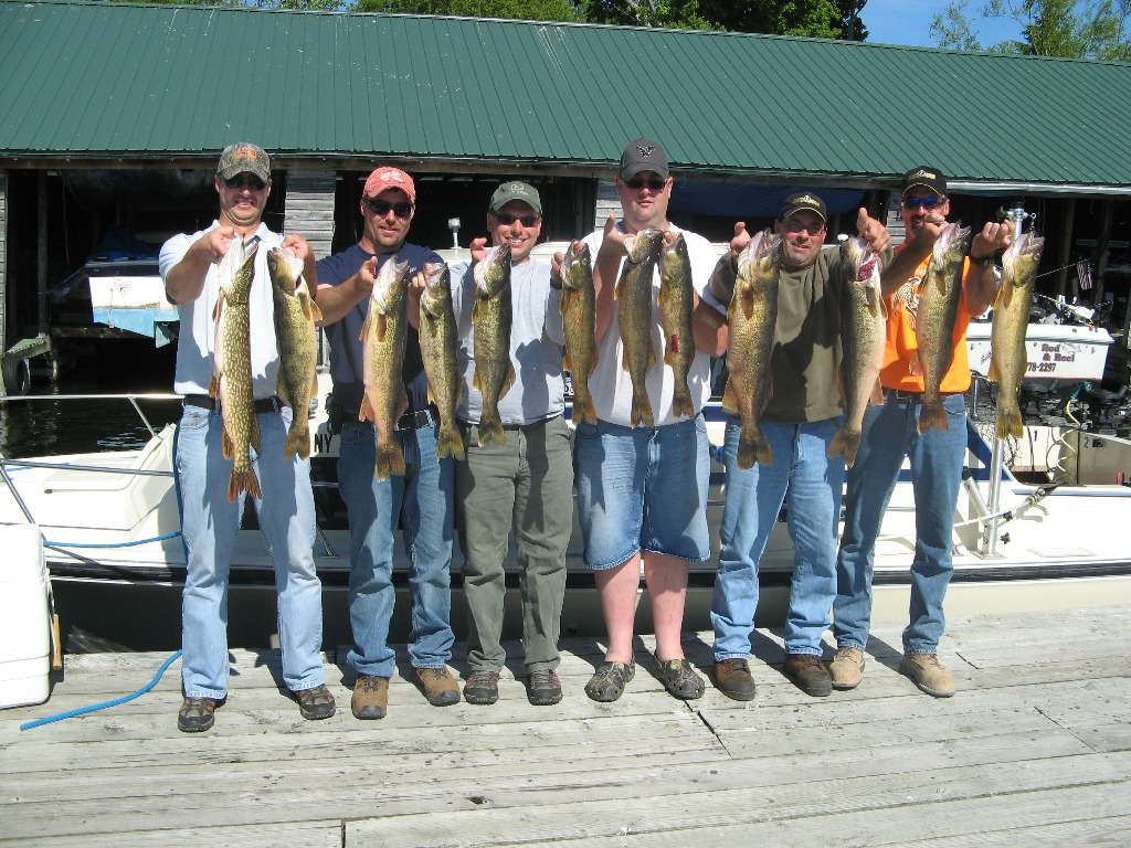 Henderson Harbor Fishing with Milky Way Charters - Ben Pate and buddies holding their trophy walleye catch along with 1 Pike